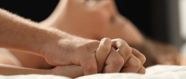 couple faisant l'amour main liée